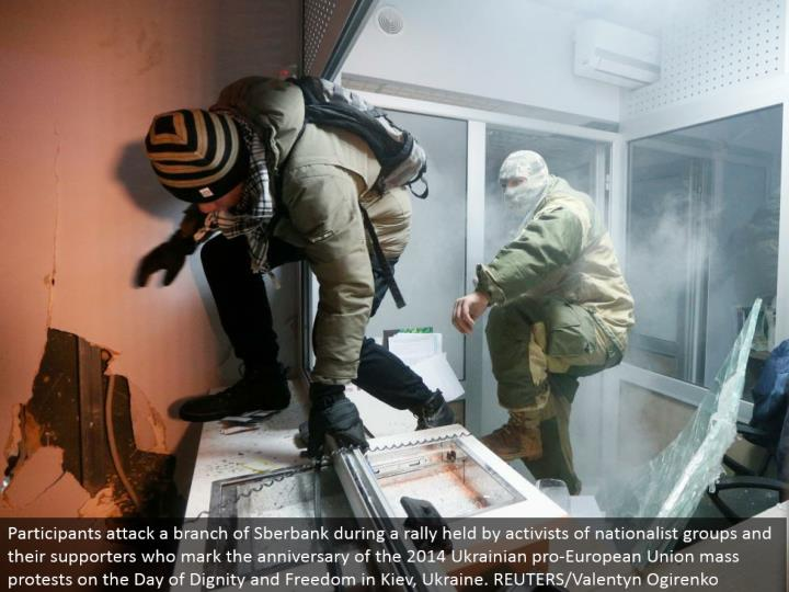 Participants assault a branch of Sberbank amid a rally held by activists of patriot gatherings and their supporters who check the commemoration of the 2014 Ukrainian genius European Union mass challenges on the Day of Dignity and Freedom in Kiev, Ukraine. REUTERS/Valentyn Ogirenko