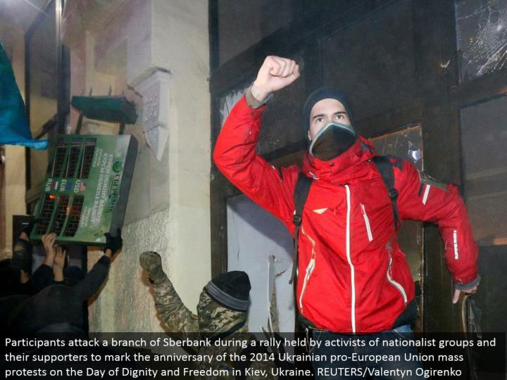Participants assault a branch of Sberbank amid a rally held by activists of patriot gatherings and their supporters to stamp the commemoration of the 2014 Ukrainian star European Union mass dissents on the Day of Dignity and Freedom in Kiev, Ukraine. REUTERS/Valentyn Ogirenko