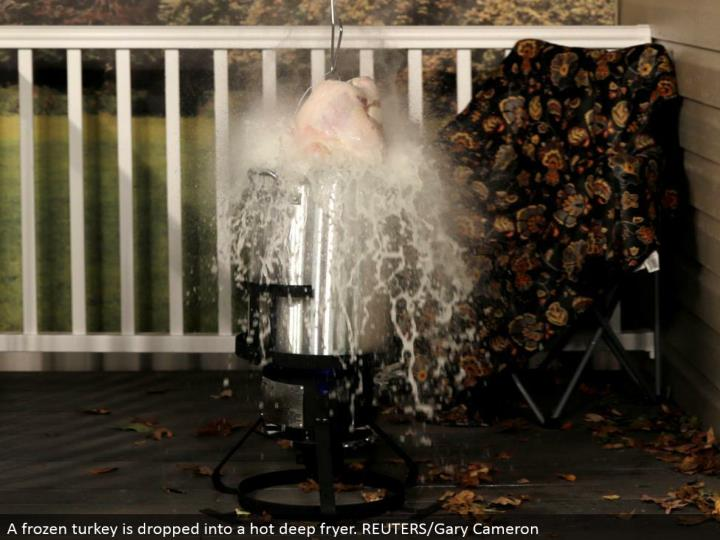 A solidified turkey is dropped into a hot profound fryer. REUTERS/Gary Cameron