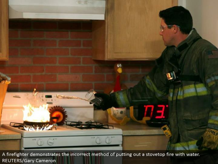 A firefighter shows the erroneous technique for putting out a stovetop fire with water. REUTERS/Gary Cameron