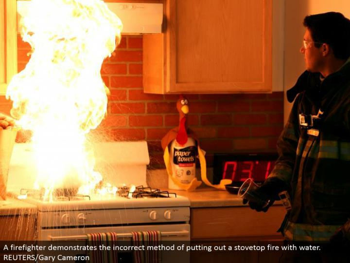 A firefighter shows the off base strategy for putting out a stovetop fire with water. REUTERS/Gary Cameron