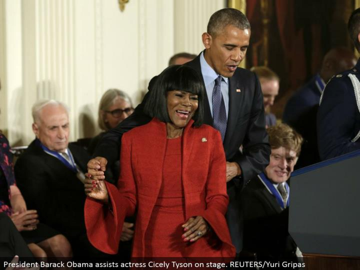 President Barack Obama helps performer Cicely Tyson in front of an audience. REUTERS/Yuri Gripas