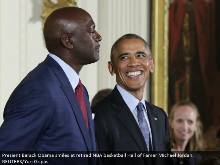 Presient Barack Obama grins at resigned NBA b-ball Hall of Famer Michael Jordan. REUTERS/Yuri Gripas