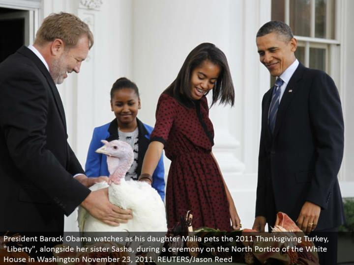 """President Barack Obama looks as his little girl Malia pets the 2011 Thanksgiving Turkey, """"Freedom"""", close by her sister Sasha, amid a function on the North Portico of the White House in Washington November 23, 2011. REUTERS/Jason Reed"""