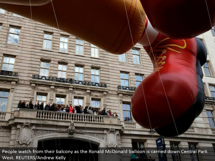 People watch from their overhang as the Ronald McDonald inflatable is conveyed down Central Park West. REUTERS/Andrew Kelly