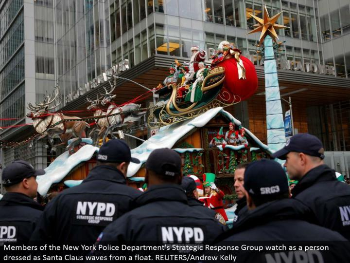 Members of the New York Police Department's Strategic Response Group look as a man dressed as Santa Claus waves from a buoy. REUTERS/Andrew Kelly