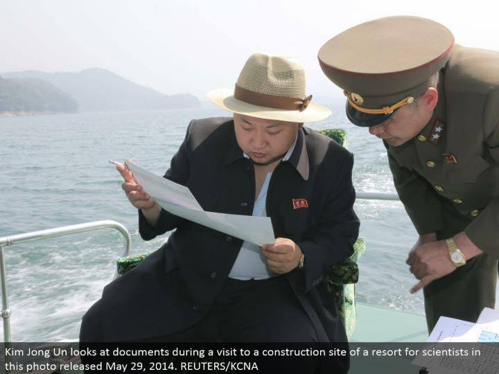 Kim Jong Un takes a gander at reports amid a visit to a development site of a resort for researchers in this photograph discharged May 29, 2014. REUTERS/KCNA