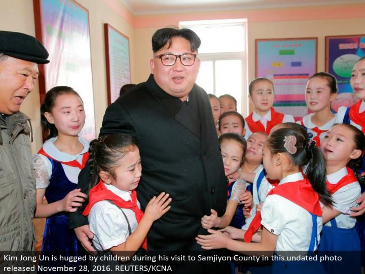 Kim Jong Un is embraced by kids amid his visit to Samjiyon County in this undated photograph discharged November 28, 2016. REUTERS/KCNA