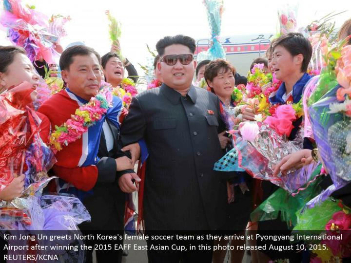 Kim Jong Un welcomes North Korea's female soccer group as they touch base at Pyongyang International Airport in the wake of winning the 2015 EAFF East Asian Cup, in this photograph discharged August 10, 2015. REUTERS/KCNA