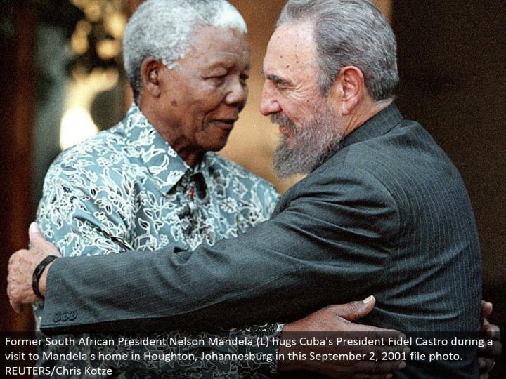 Former South African President Nelson Mandela (L) embraces Cuba's President Fidel Castro amid a visit to Mandela's home in Houghton, Johannesburg in this September 2, 2001 document photograph. REUTERS/Chris Kotze