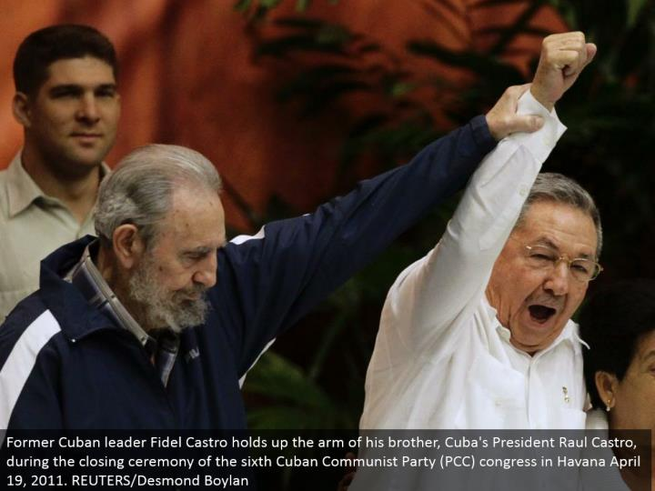 Former Cuban pioneer Fidel Castro holds up the arm of his sibling, Cuba's President Raul Castro, amid the end function of the 6th Cuban Communist Party (PCC) congress in Havana April 19, 2011. REUTERS/Desmond Boylan