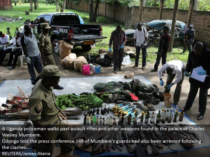 A Uganda policeman strolls past ambush rifles and different weapons found in the royal residence of Charles Wesley Mumbere.  Odongo told the public interview 149 of Mumbere's gatekeepers had additionally been captured taking after the conflicts.  REUTERS/James Akena