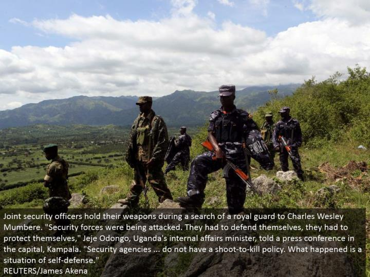 Joint security officers hold their weapons amid a hunt of a regal protect to Charles Wesley Mumbere....