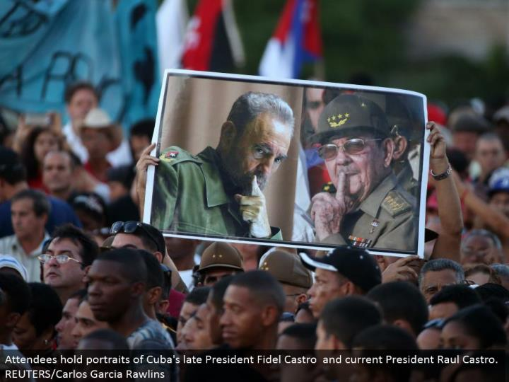 Attendees hold representations of Cuba's late President Fidel Castro and current President Raul Castro. REUTERS/Carlos Garcia Rawlins