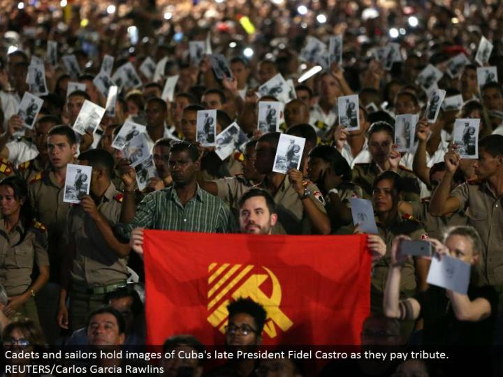 Cadets and mariners hold pictures of Cuba's late President Fidel Castro as they pay tribute. REUTERS...