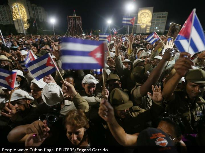 People wave Cuban banners. REUTERS/Edgard Garrido