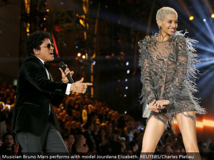 Musician Bruno Mars performs with model Jourdana Elizabeth. REUTERS/Charles Platiau