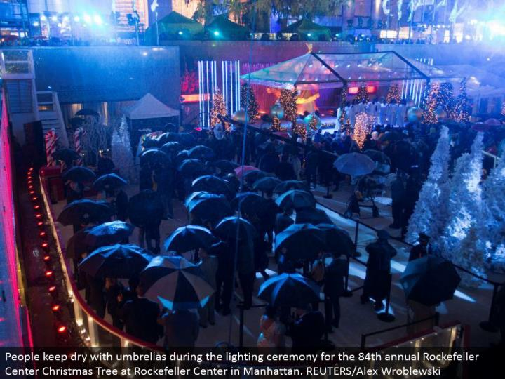 People keep dry with umbrellas amid the lighting function for the 84th yearly Rockefeller Center Christmas Tree at Rockefeller Center in Manhattan. REUTERS/Alex Wroblewski