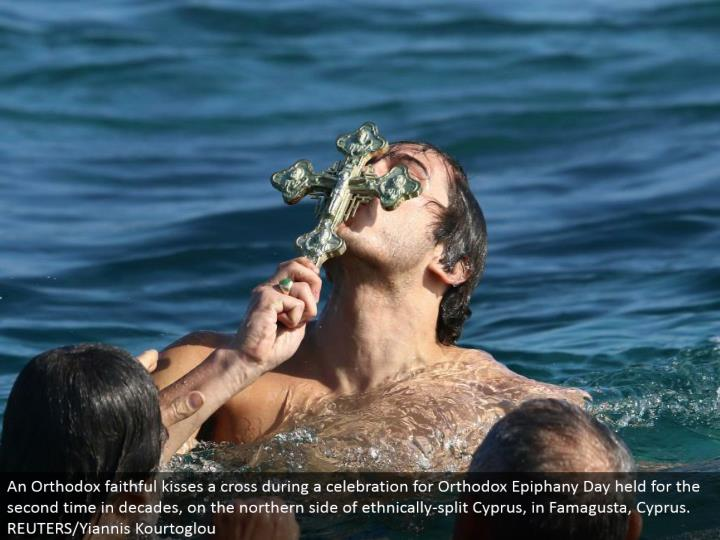 An Orthodox reliable kisses a cross amid a festival for Orthodox Epiphany Day held for the second ti...