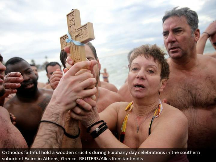 Orthodox reliable hold a wooden cross amid Epiphany day festivities in the southern suburb of Faliro in Athens, Greece. REUTERS/Alkis Konstantinidis