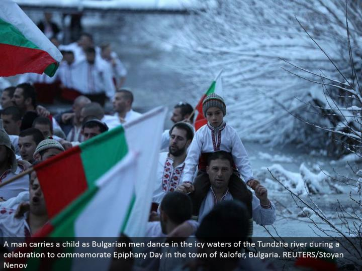 A man conveys a kid as Bulgarian men move in the frigid waters of the Tundzha waterway amid a festival to celebrate Epiphany Day in the town of Kalofer, Bulgaria. REUTERS/Stoyan Nenov