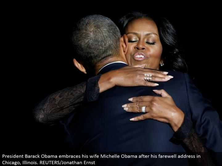President Barack Obama grasps his better half Michelle Obama after his goodbye address in Chicago, I...