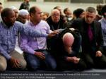 a man is console as he cries amid a memorial