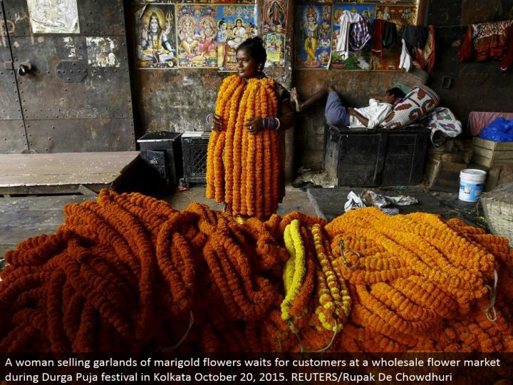 A lady offering wreaths of marigold blooms sits tight for clients at a discount blossom showcase amid Durga Puja celebration in Kolkata October 20, 2015. REUTERS/Rupak De Chowdhuri