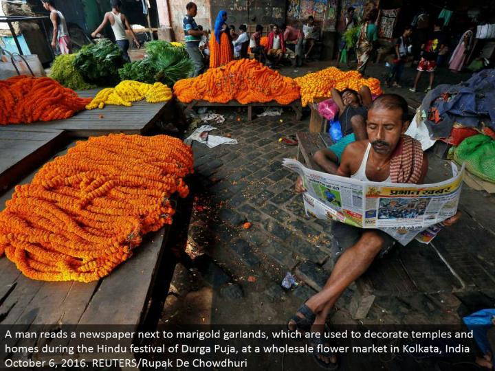 A man peruses a daily paper beside marigold wreaths, which are utilized to enliven sanctuaries and homes amid the Hindu celebration of Durga Puja, at a discount bloom showcase in Kolkata, India October 6, 2016. REUTERS/Rupak De Chowdhuri