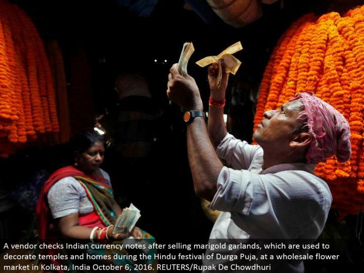 A merchant checks Indian cash notes in the wake of offering marigold festoons, which are utilized to enhance sanctuaries and homes amid the Hindu celebration of Durga Puja, at a discount bloom showcase in Kolkata, India October 6, 2016. REUTERS/Rupak De Chowdhuri