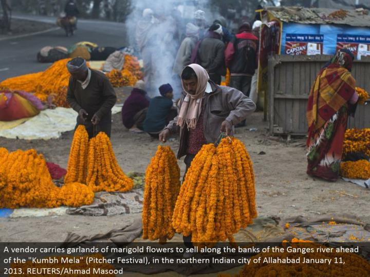"""A merchant conveys festoons of marigold blossoms to offer along the banks of the Ganges stream in front of the """"Kumbh Mela"""" (Pitcher Festival), in the northern Indian city of Allahabad January 11, 2013. REUTERS/Ahmad Masood"""