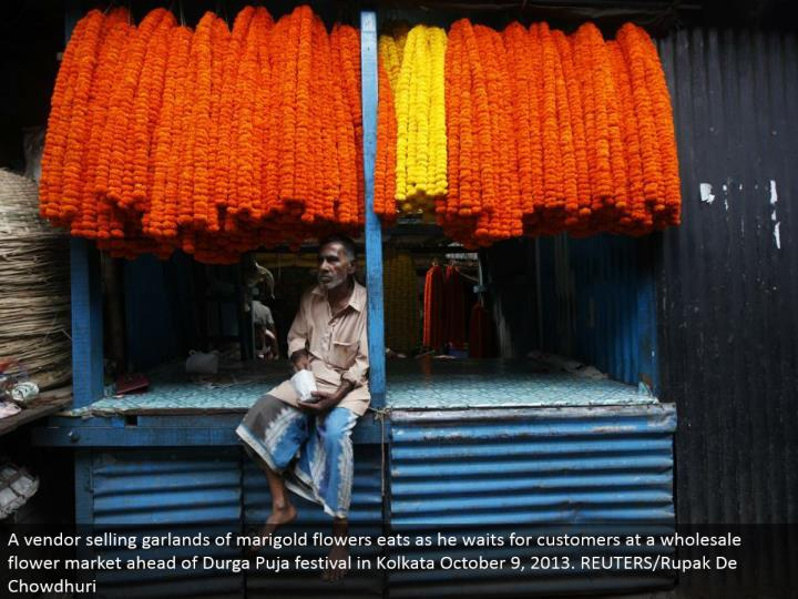 A merchant offering festoons of marigold blooms eats as he sits tight for clients at a discount blossom advertise in front of Durga Puja celebration in Kolkata October 9, 2013. REUTERS/Rupak De Chowdhuri