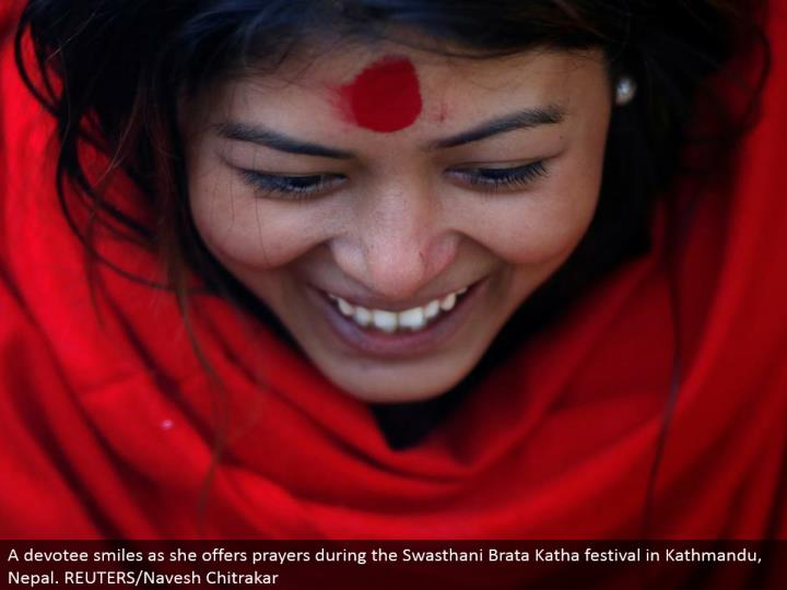 A lover grins as she offers petitions amid the Swasthani Brata Katha celebration in Kathmandu, Nepal. REUTERS/Navesh Chitrakar