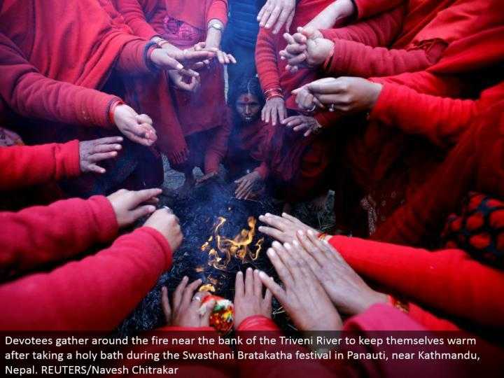 Devotees assemble around the fire close to the bank of the Triveni River to keep themselves warm in the wake of cleaning up amid the Swasthani Bratakatha celebration in Panauti, close Kathmandu, Nepal. REUTERS/Navesh Chitrakar