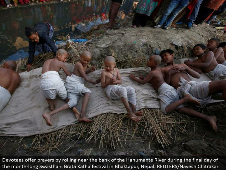 Devotees offer petitions by moving close to the bank of the Hanumante River amid the last day of the month-long Swasthani Brata Katha celebration in Bhaktapur, Nepal. REUTERS/Navesh Chitrakar