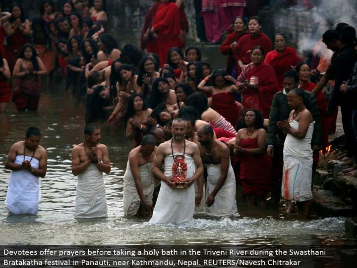 Devotees offer supplications before cleaning up in the Triveni River amid the Swasthani Bratakatha celebration in Panauti, close Kathmandu, Nepal. REUTERS/Navesh Chitrakar