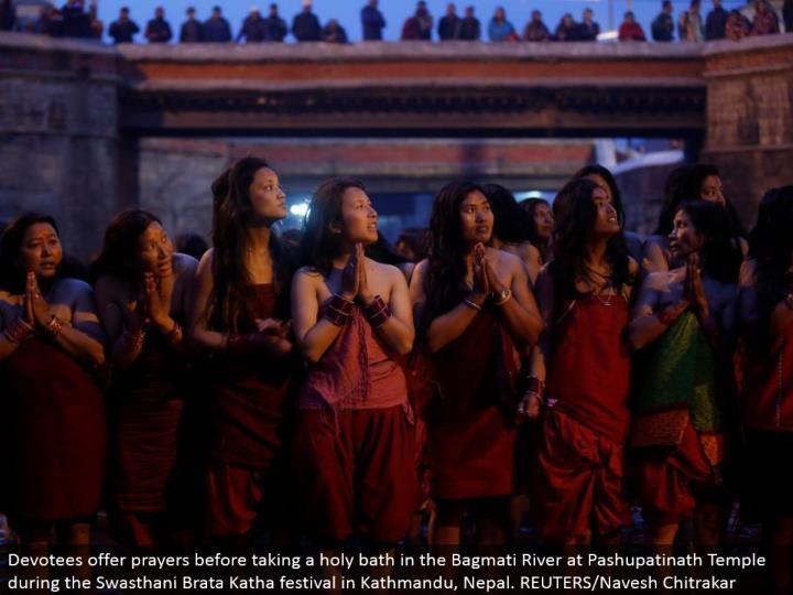 Devotees offer supplications before cleaning up in the Bagmati River at Pashupatinath Temple amid the Swasthani Brata Katha celebration in Kathmandu, Nepal. REUTERS/Navesh Chitrakar