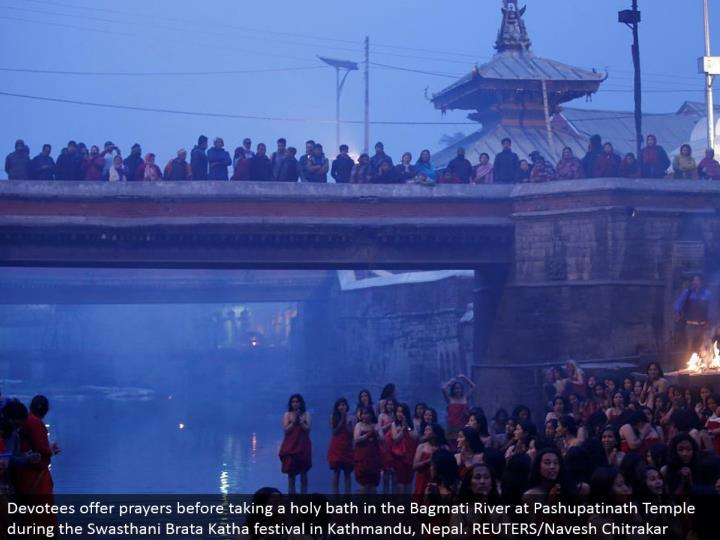 Devotees offer supplications before washing up in the Bagmati River at Pashupatinath Temple amid the Swasthani Brata Katha celebration in Kathmandu, Nepal. REUTERS/Navesh Chitrakar