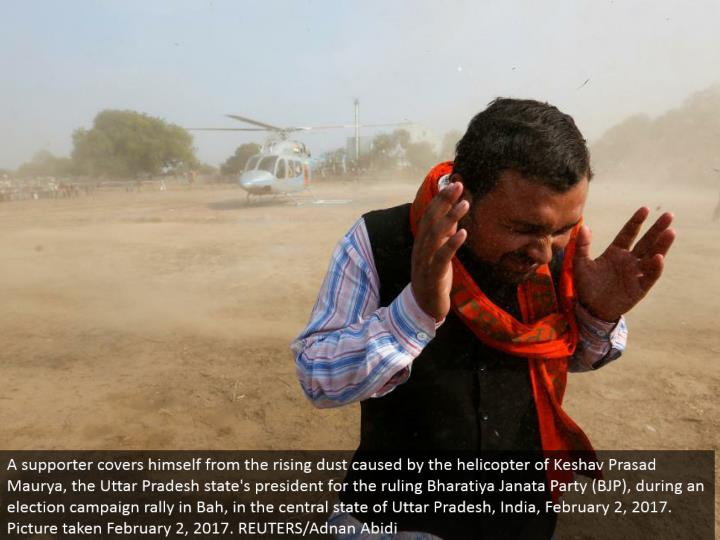 A supporter covers himself from the rising dust brought on by the helicopter of Keshav Prasad Maurya, the Uttar Pradesh state's leader for the decision Bharatiya Janata Party (BJP), amid a race battle rally in Bah, in the focal condition of Uttar Pradesh, India, February 2, 2017. Picture taken February 2, 2017. REUTERS/Adnan Abidi