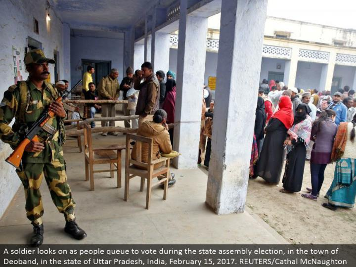 A trooper looks on as individuals line to vote amid the state get together race, in the town of Deoband, in the condition of Uttar Pradesh, India, February 15, 2017. REUTERS/Cathal McNaughton