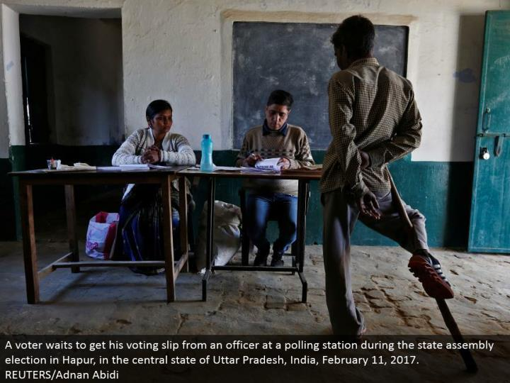 A voter holds up to get his voting slip from an officer at a surveying station amid the state get together race in Hapur, in the focal condition of Uttar Pradesh, India, February 11, 2017. REUTERS/Adnan Abidi