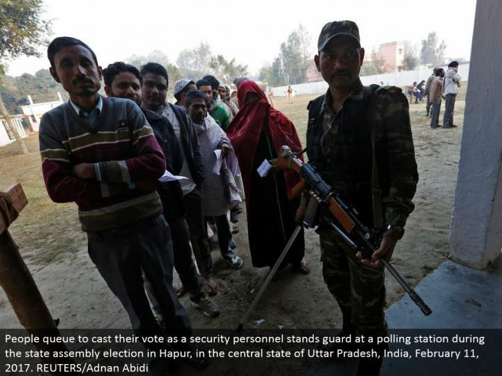 People line to give their vote a role as a security staff stands protect at a surveying station amid the state get together decision in Hapur, in the focal condition of Uttar Pradesh, India, February 11, 2017. REUTERS/Adnan Abidi