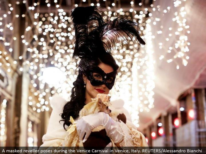 A covered reveler postures amid the Venice Carnival in Venice, Italy. REUTERS/Alessandro Bianchi
