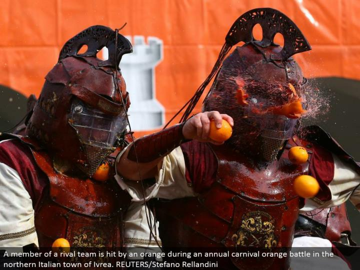 A individual from an opponent group is hit by an orange amid a yearly jubilee orange fight in the northern Italian town of Ivrea. REUTERS/Stefano Rellandini