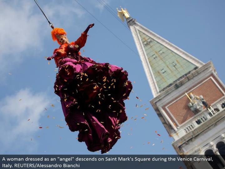 """A lady dressed as a """"blessed messenger"""" slides on Saint Mark's Square amid the Venice Carnival, Italy. REUTERS/Alessandro Bianchi"""