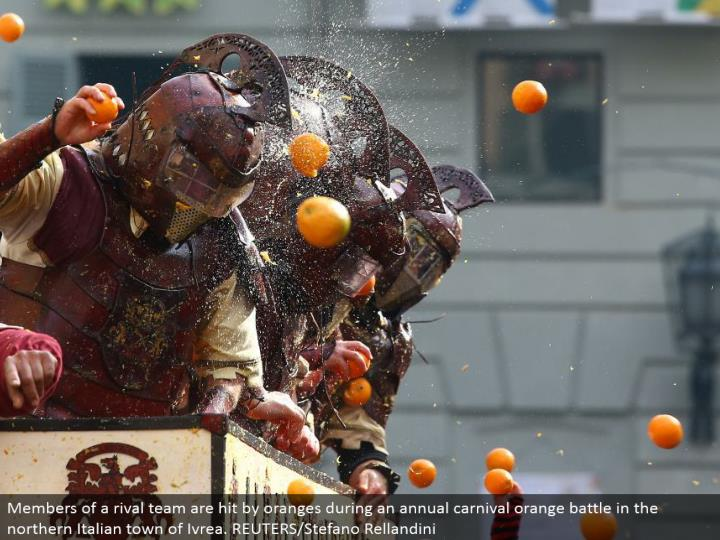 Members of an opponent group are hit by oranges amid a yearly fair orange fight in the northern Italian town of Ivrea. REUTERS/Stefano Rellandini