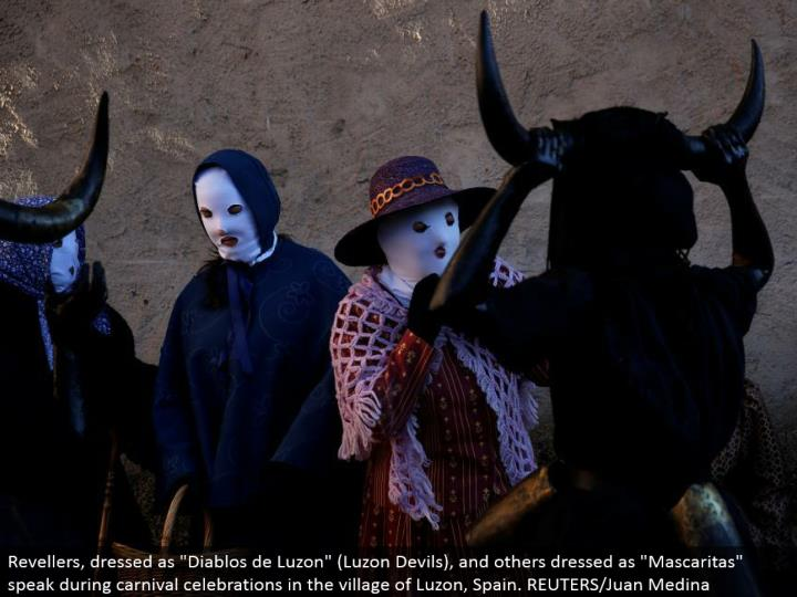 """Revellers, dressed as """"Diablos de Luzon"""" (Luzon Devils), and others dressed as """"Mascaritas"""" talk amid jubilee festivities in the town of Luzon, Spain. REUTERS/Juan Medina"""