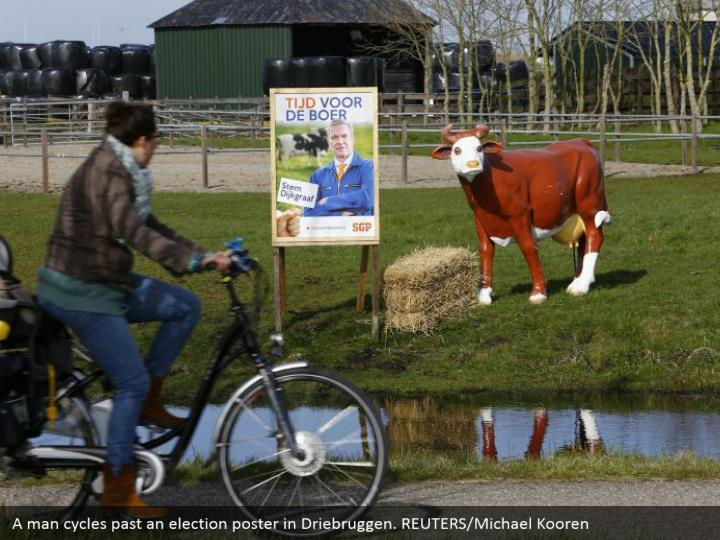 A man cycles past a race notice in Driebruggen. REUTERS/Michael Kooren