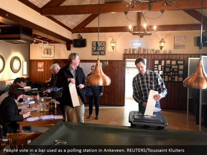 People vote in a bar utilized as a surveying station in Ankeveen. REUTERS/Toussaint Kluiters