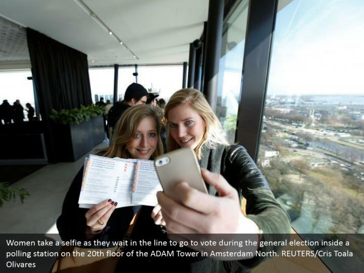 Women take a selfie as they hold up in the line to go to vote amid the general decision inside a surveying station on the twentieth floor of the ADAM Tower in Amsterdam North. REUTERS/Cris Toala Olivares